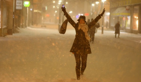 Европейцы во время снегопада ходят по городу пешком и радуются зиме